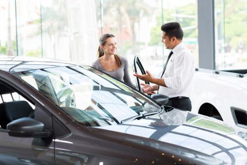 salesman opening car door for woman at dealership
