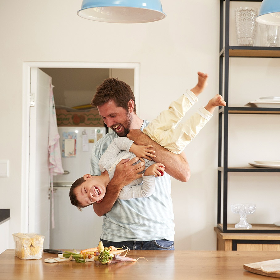 father holding son upside down in kitchen