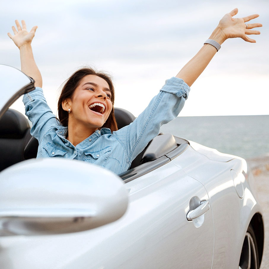 girl in a convertible car with her hands in the air