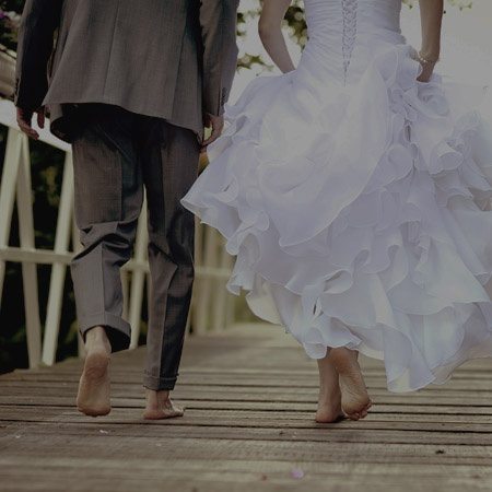bride and groom walking barefoot across bridge