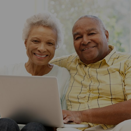 couple on couch using laptop