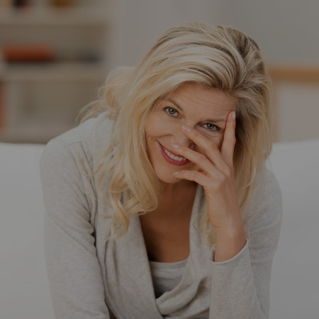 woman on couch smiling shyly
