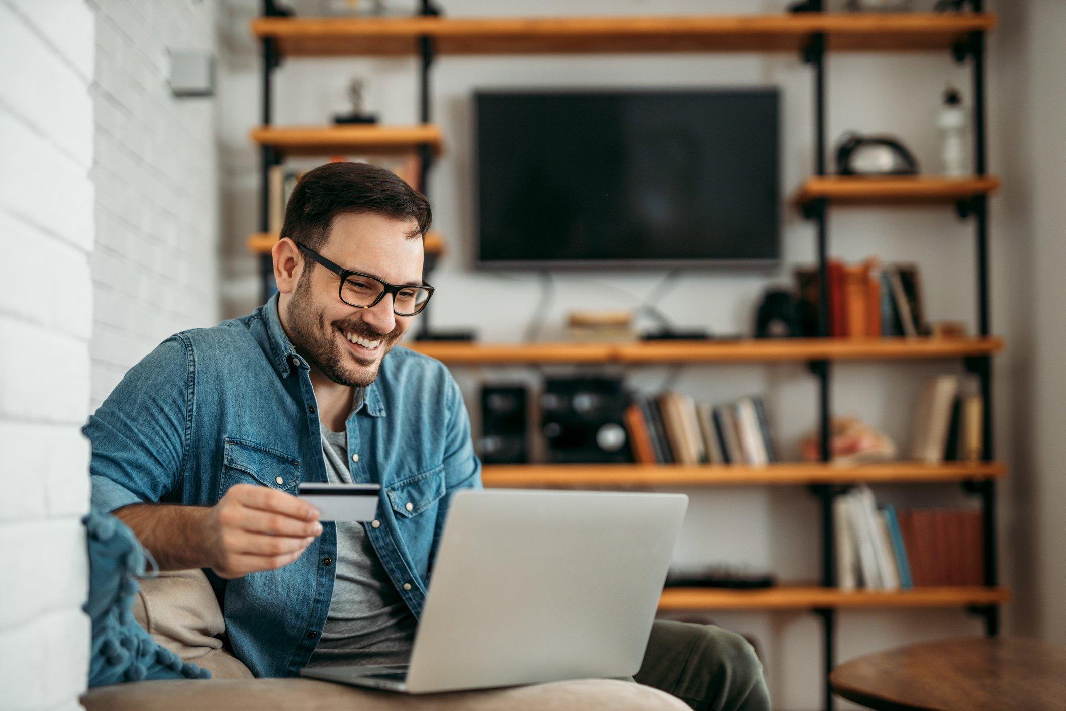 Man paying utility bills on laptop using his debit card