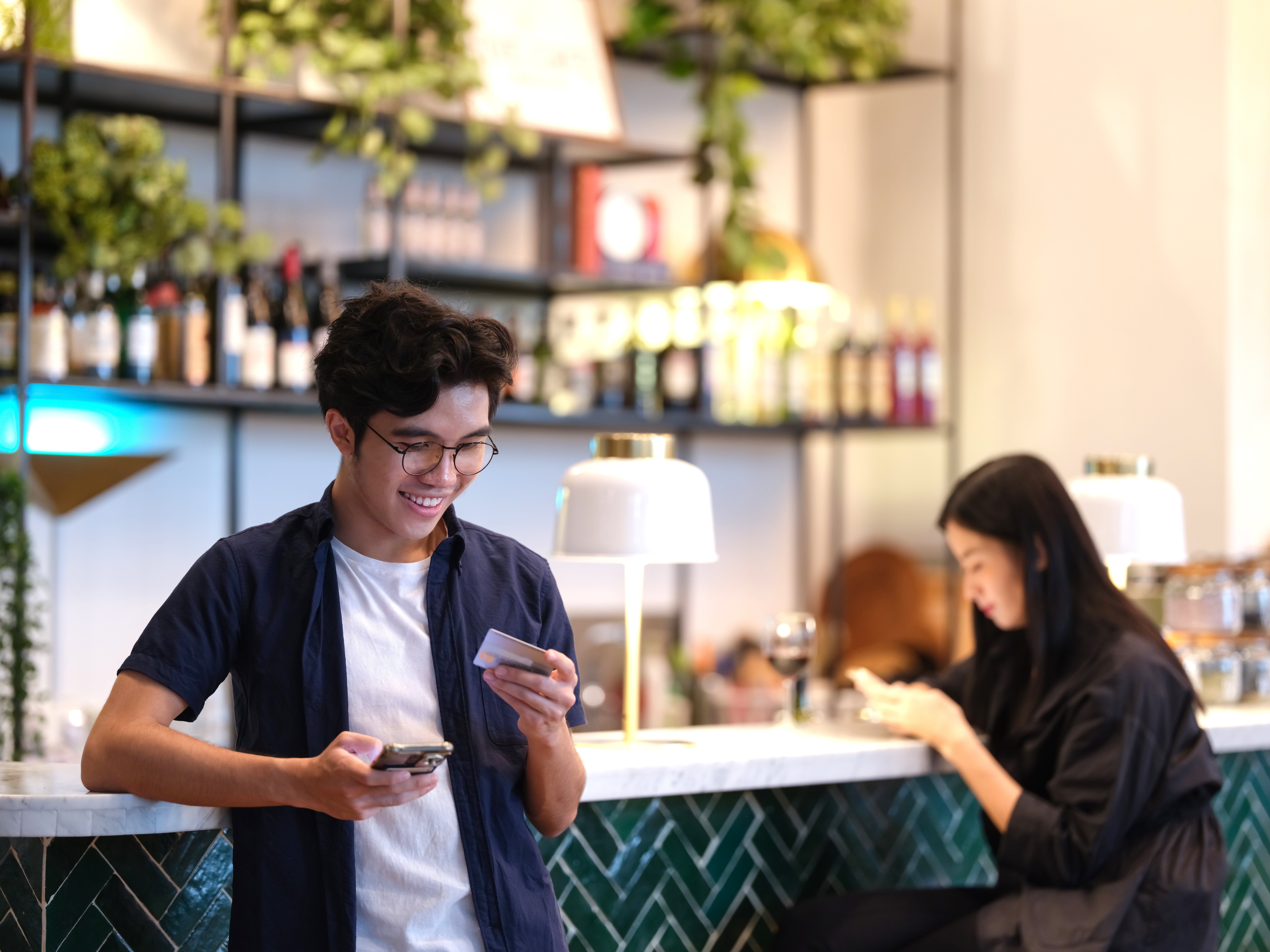 young man using his cellphone to complete online banking transaction