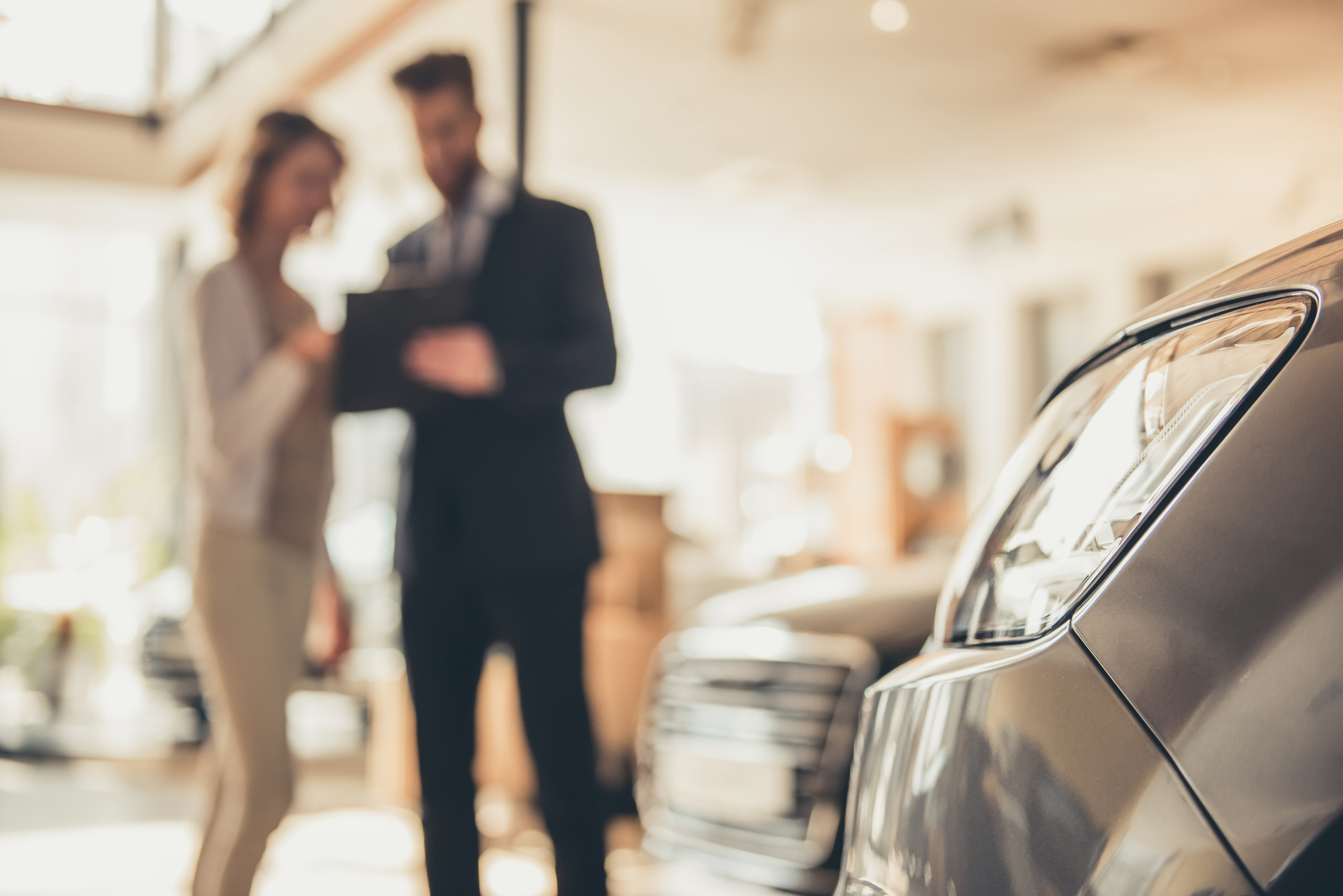 car salesman reviewing current auto loan rates in Texas with potential buyer