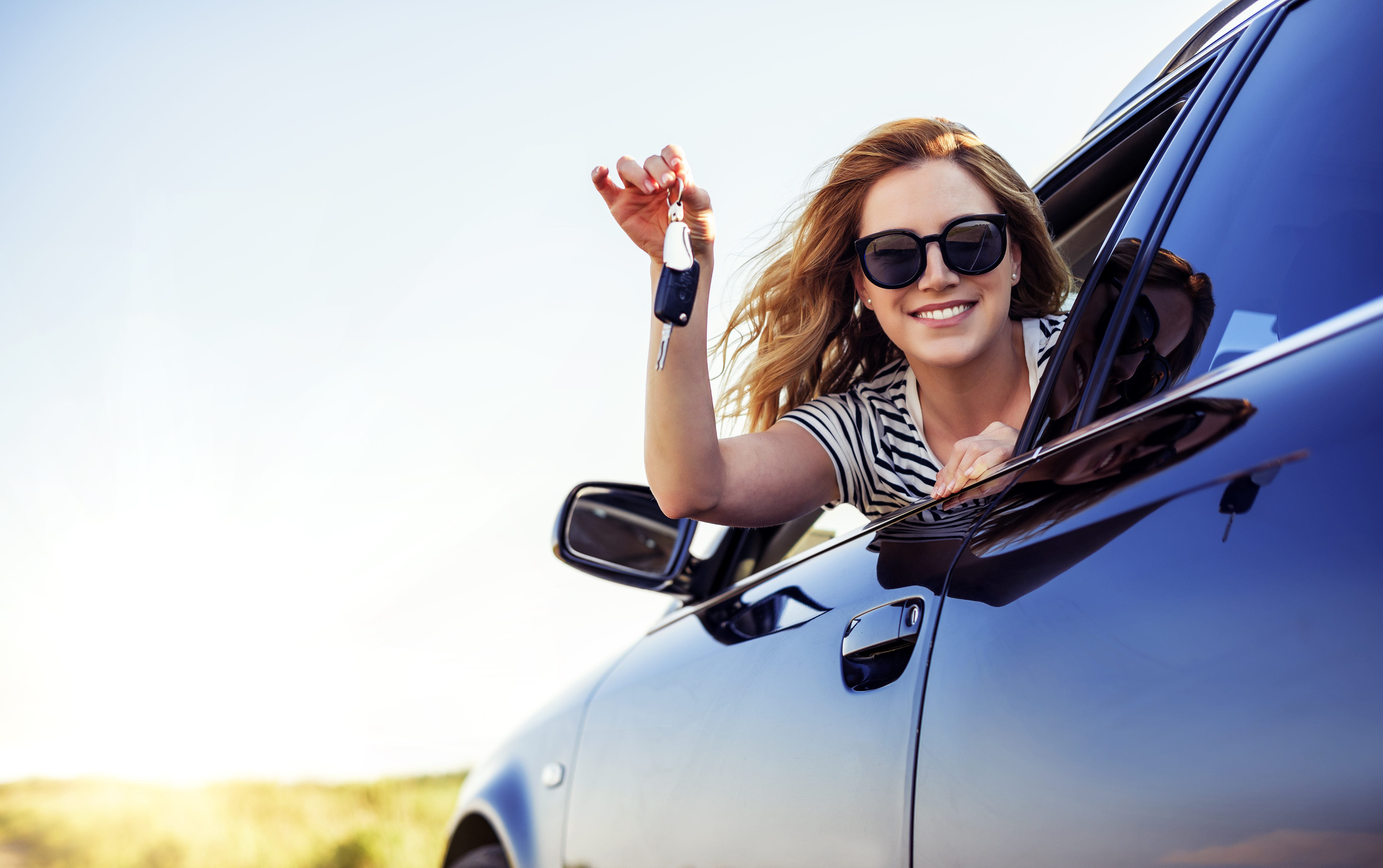 woman sitting in new car holding keys out window